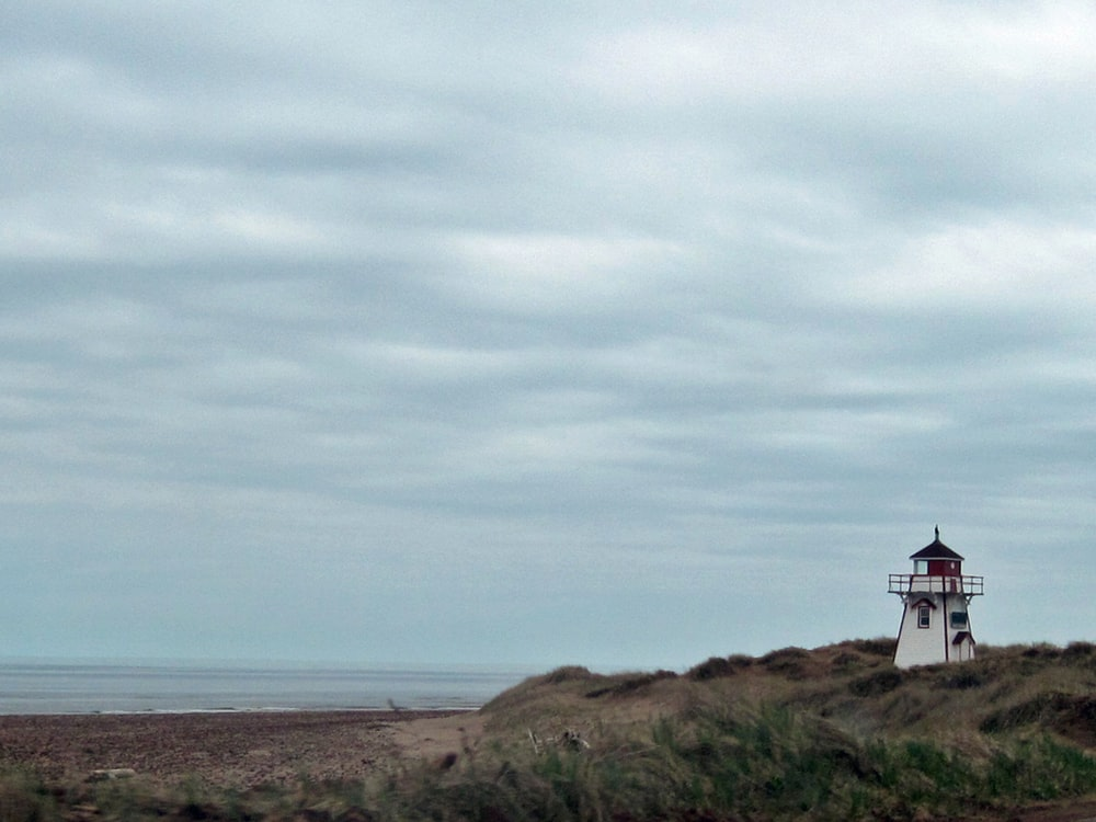 lighthouse near shore during daytime