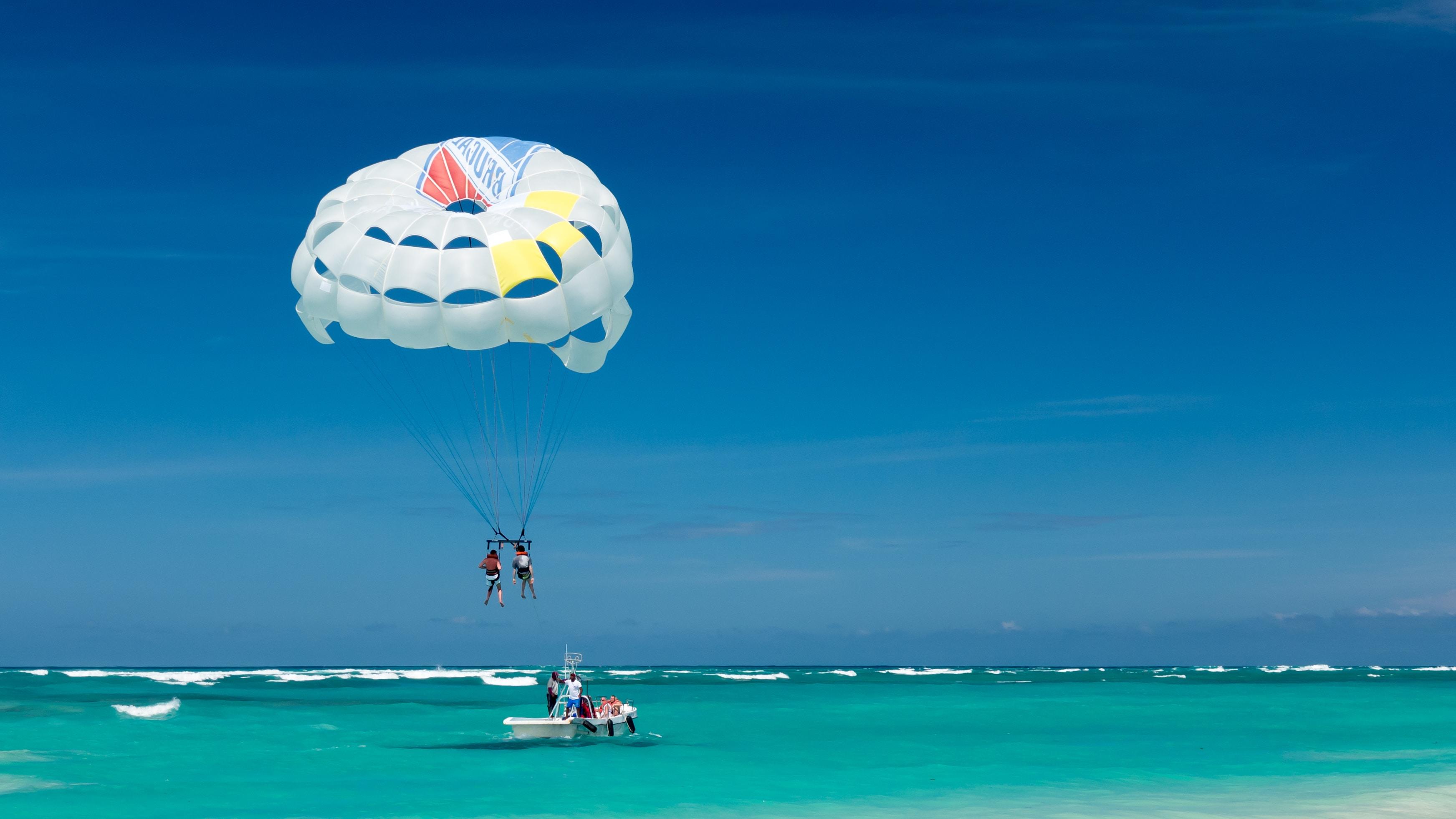 two person riding parachute near beach