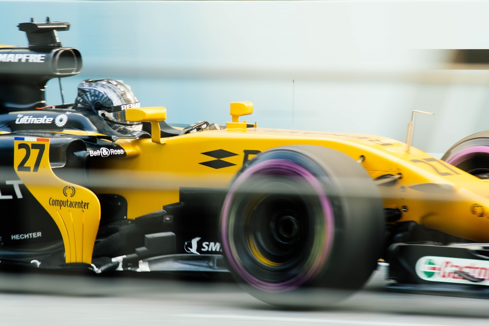 sports photography of yellow and black F1 race car