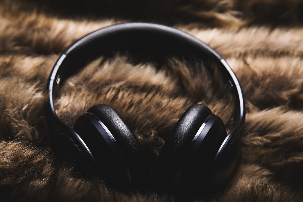 black headphones on brown textile