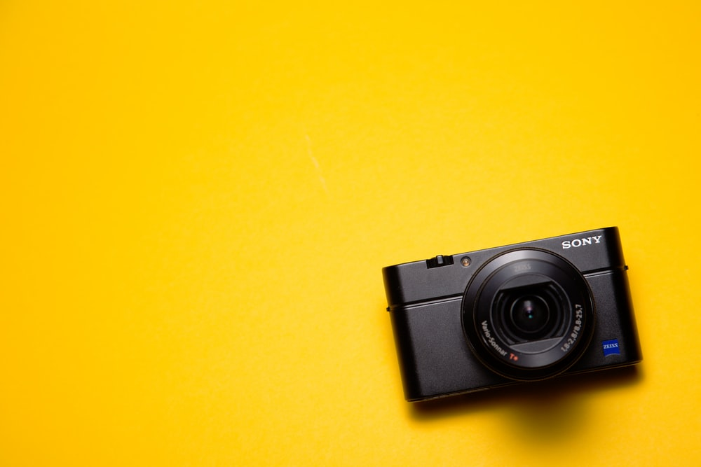 black Sony point-and-shoot camera on yellow surface