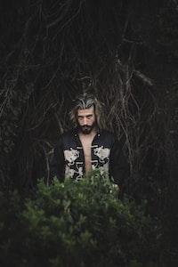 man standing behind bush