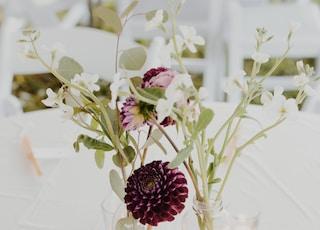 white flower arrangement on glass bottle on tabletop