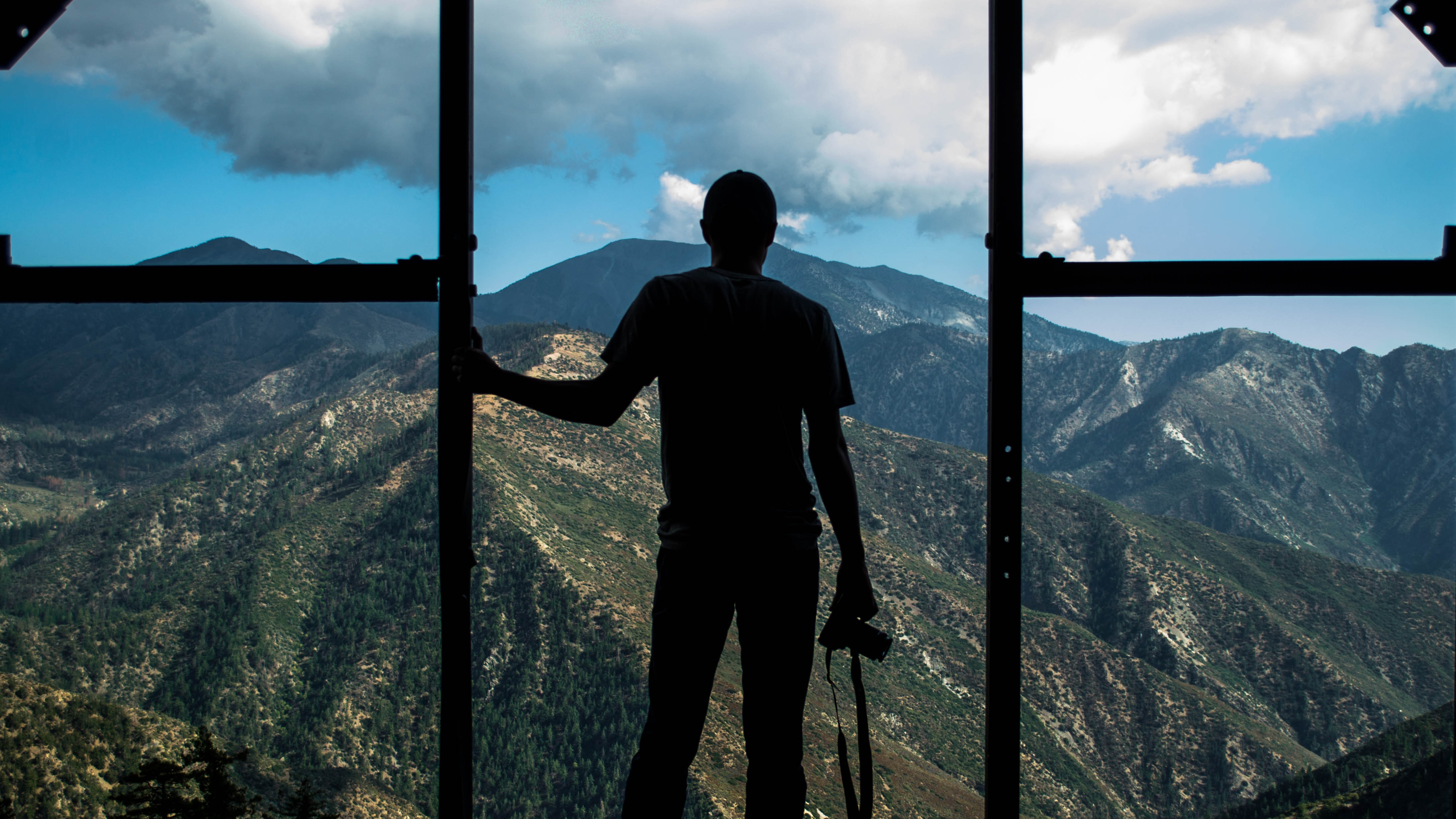 silhouette photo of person standing near door overlooking mountain during daytime