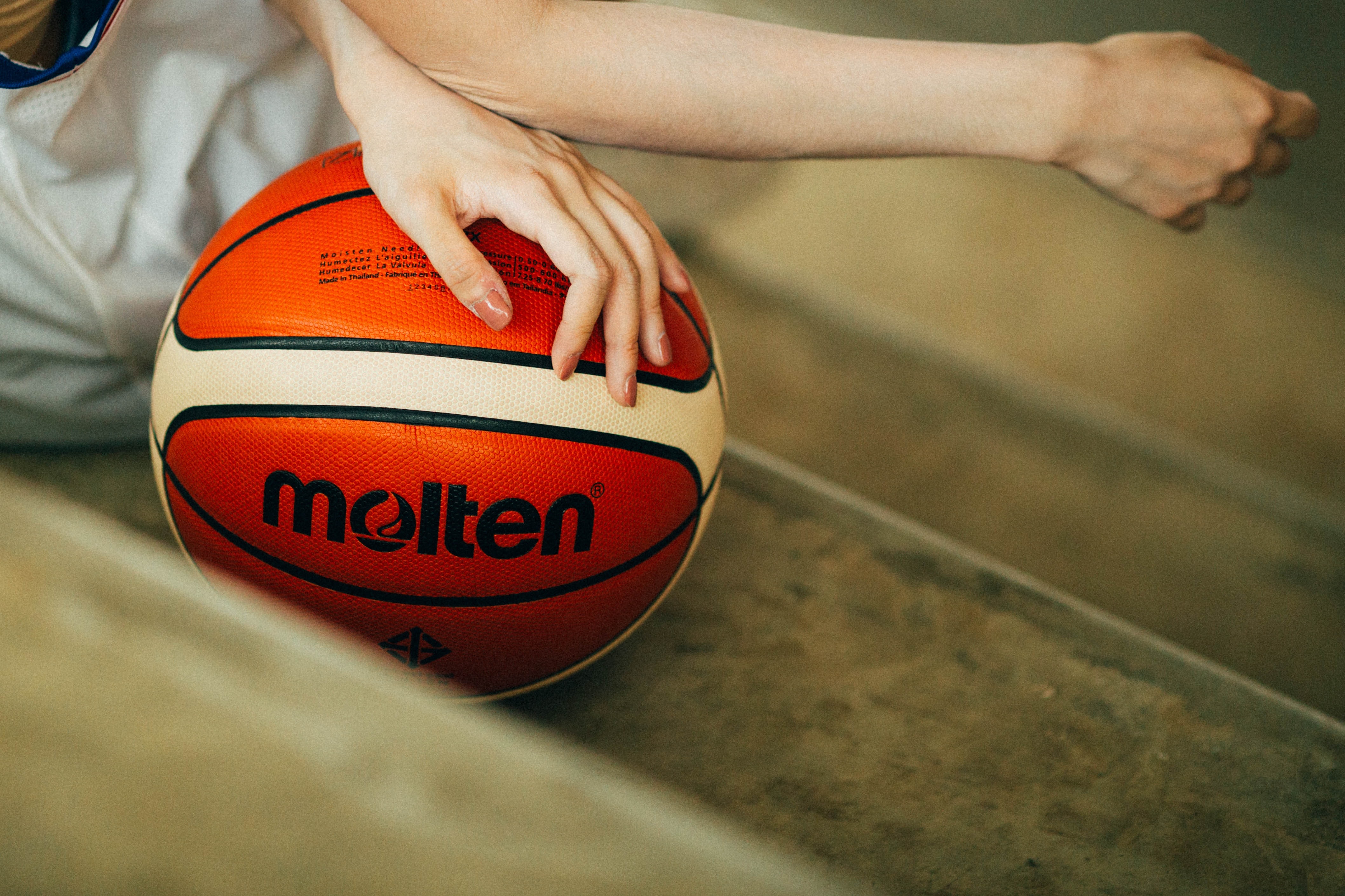 person holding red and white Molten basketball ball
