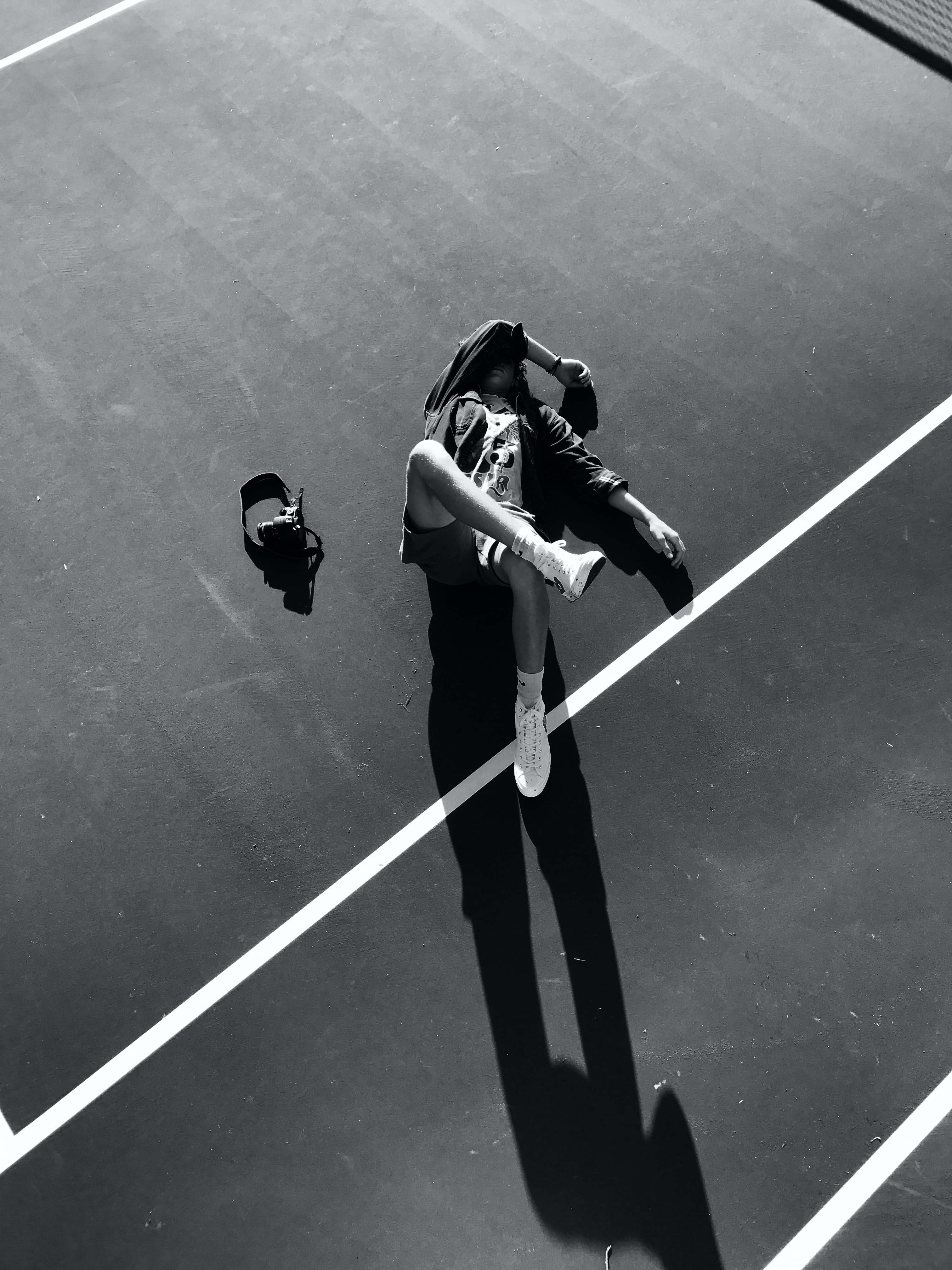 grayscale photo of athlete lying down on court