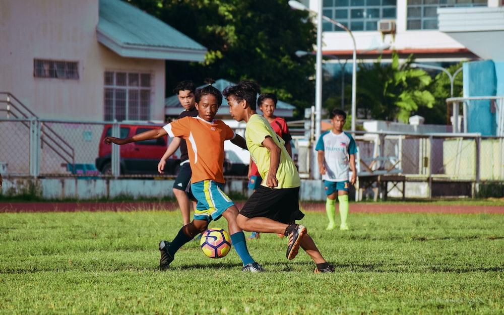 men's playing soccer during daytime