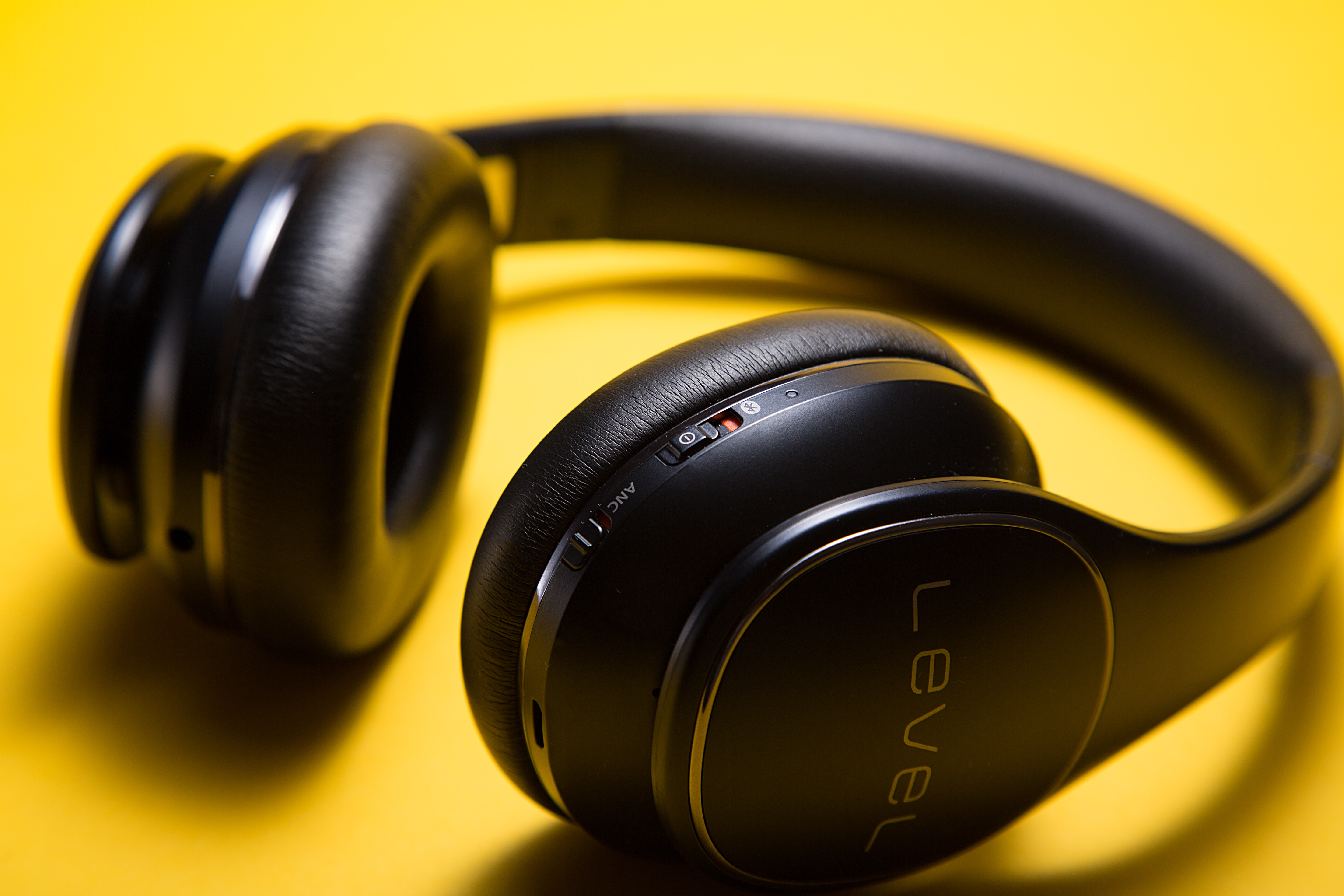 black Level wireless headphones on yellow surface