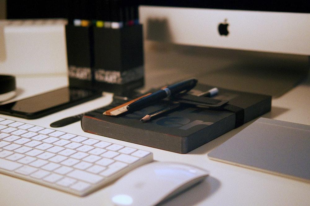 white magic mouse near apple keyboard