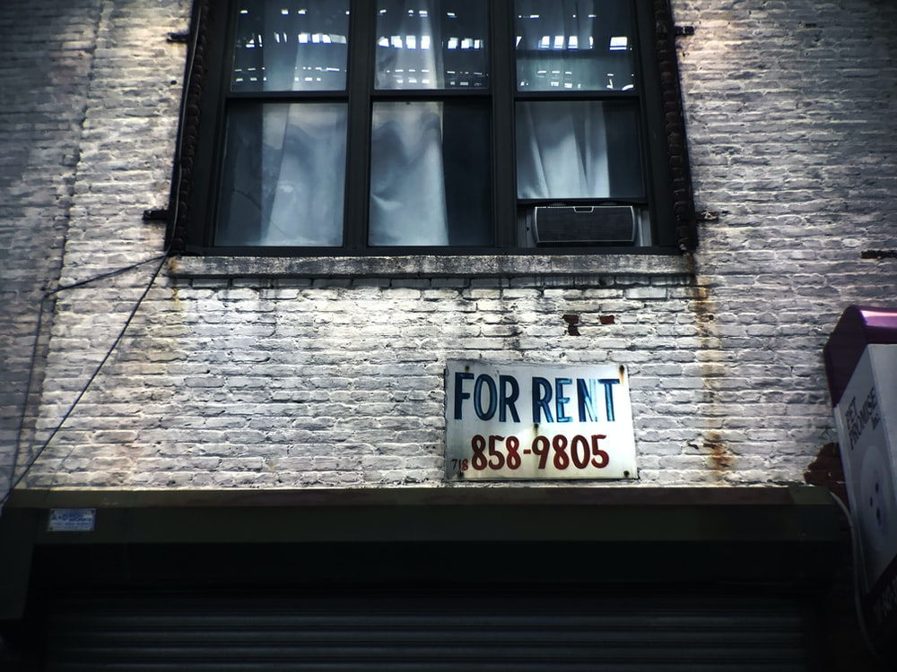 for rent sign on wall below window glass of building
