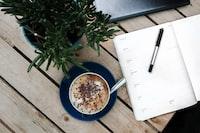 pen on printer paper beside a cappuccino