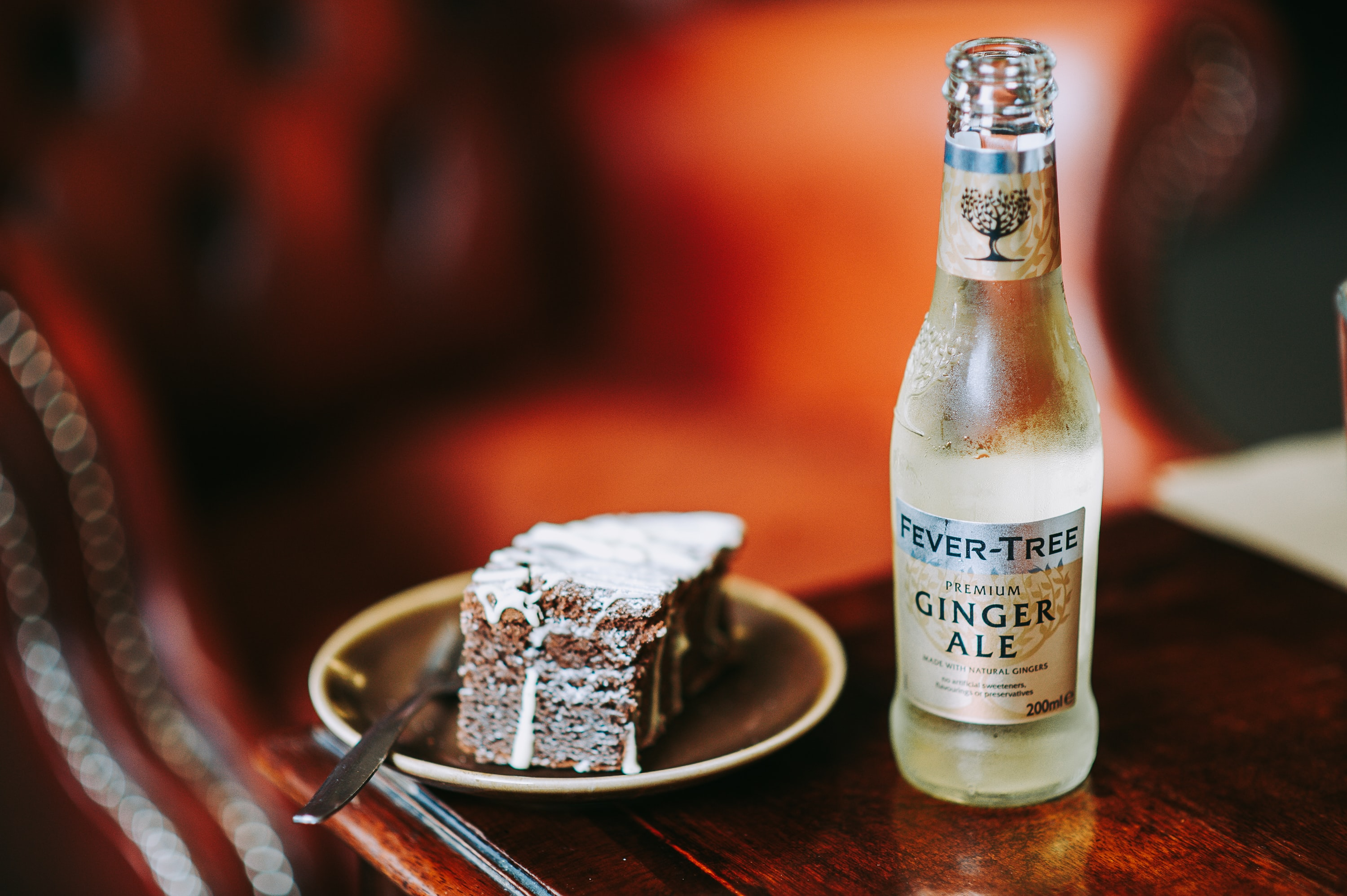 sliced cake on brown saucer beside fever-tree ginger ale bottle