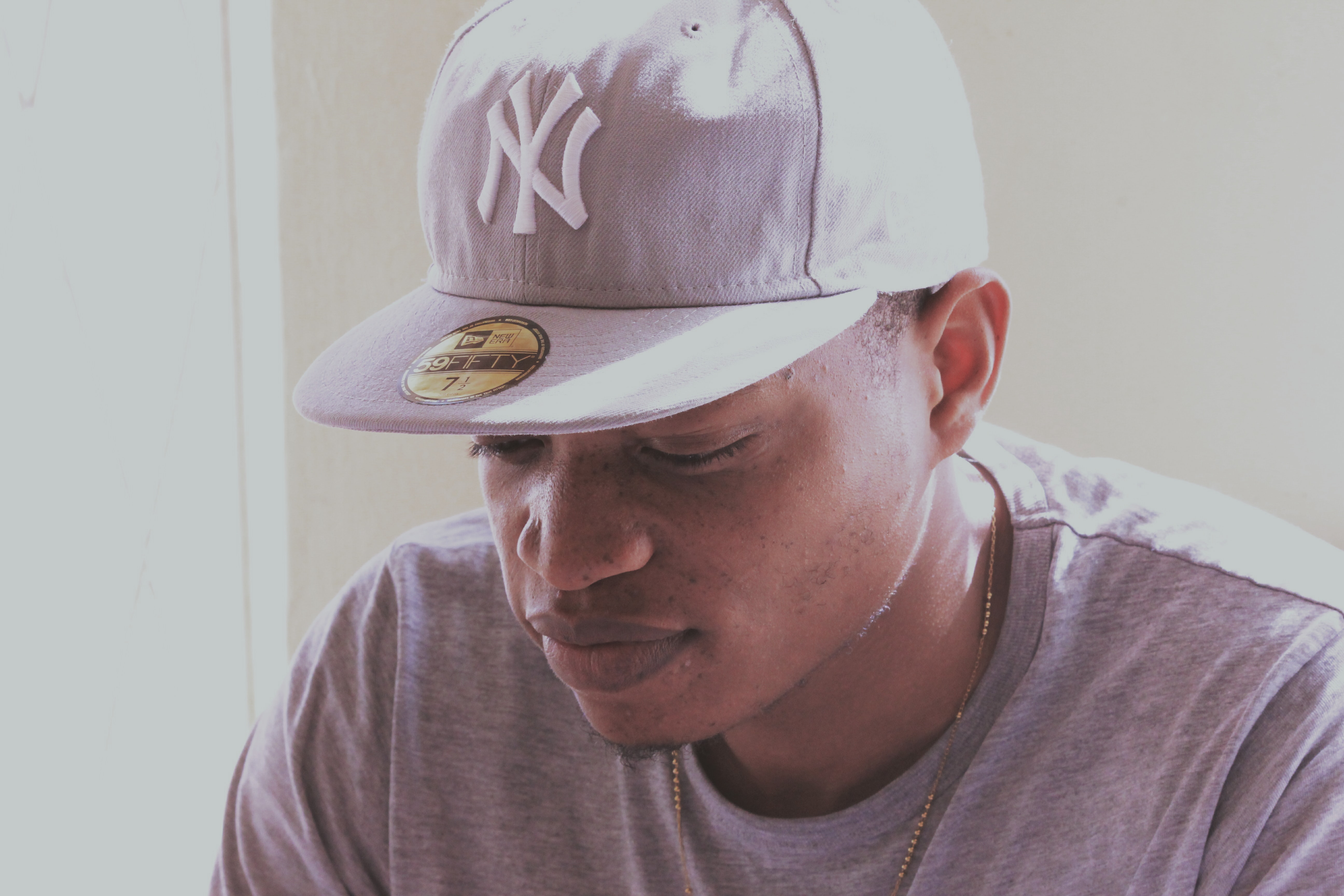 man wearing gray crew-neck shirt and fitted cap