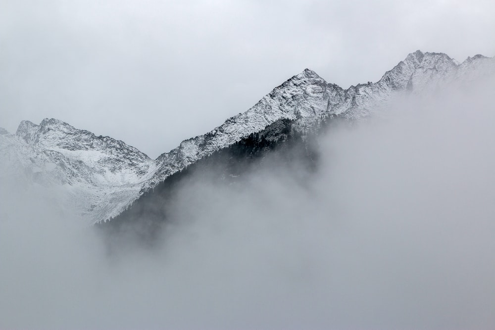 snow covered mountains near clouds