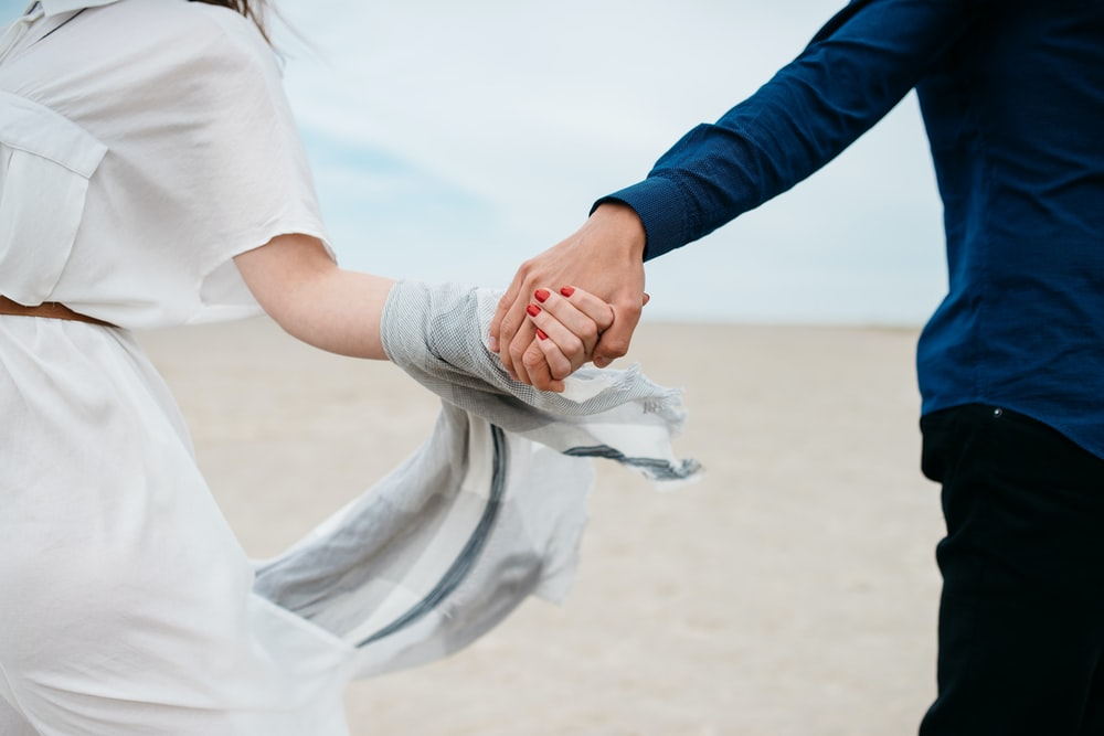 man and woman holding hands together in field during daytime