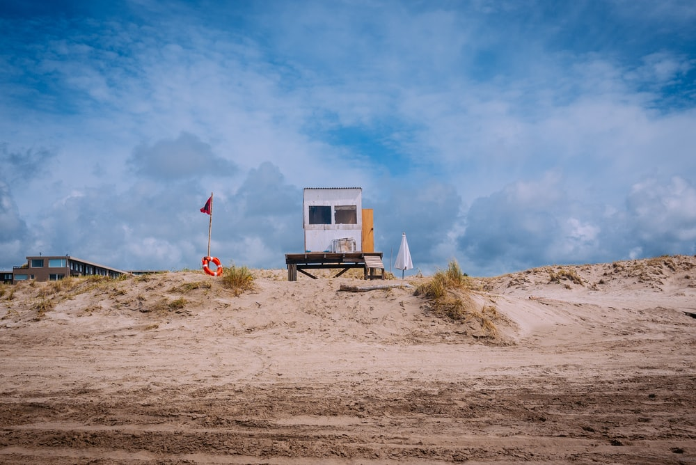 white lifeguard shed beside flag during daytime