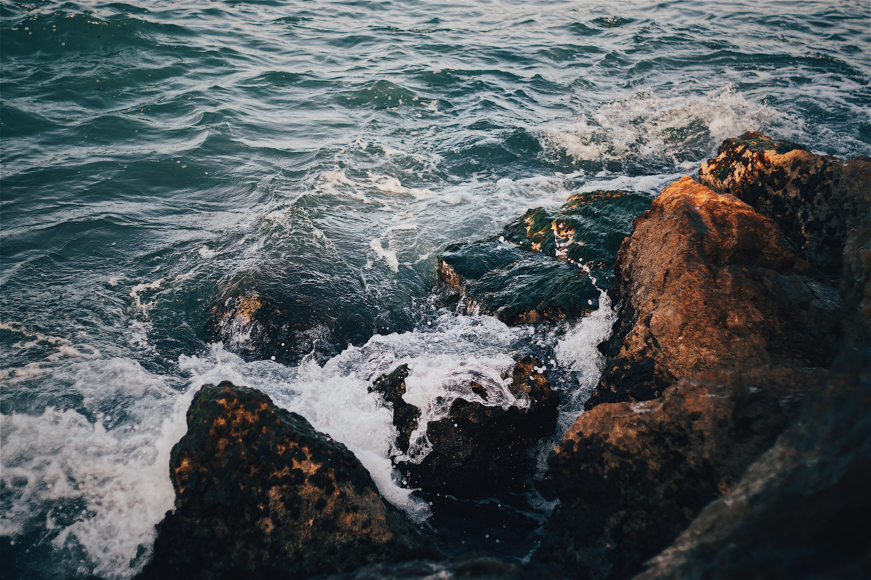 water splashing into coastal rocks