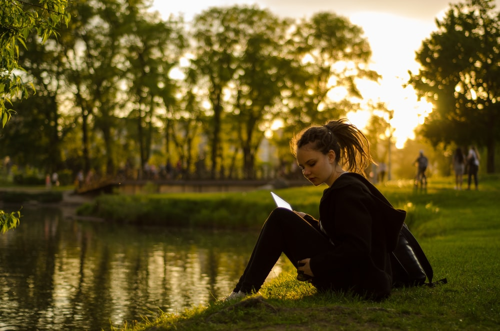 woman sitting on grass field beside body of water during golden hour