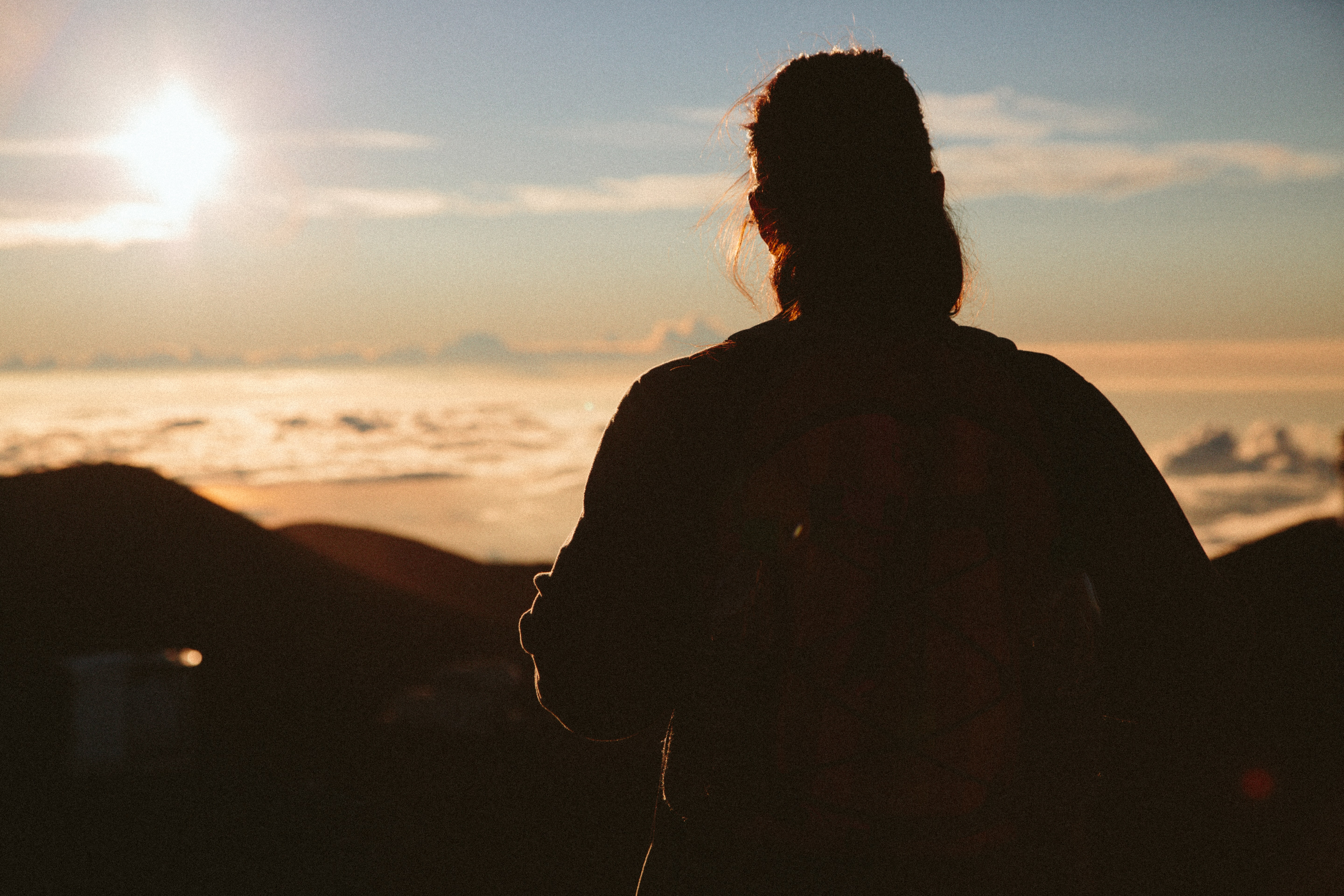 silhouette of woman facing hills