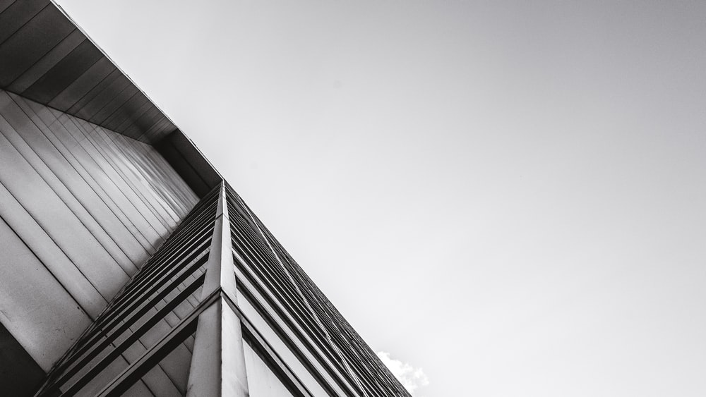low-angle grayscale photography of building under cloudy sky