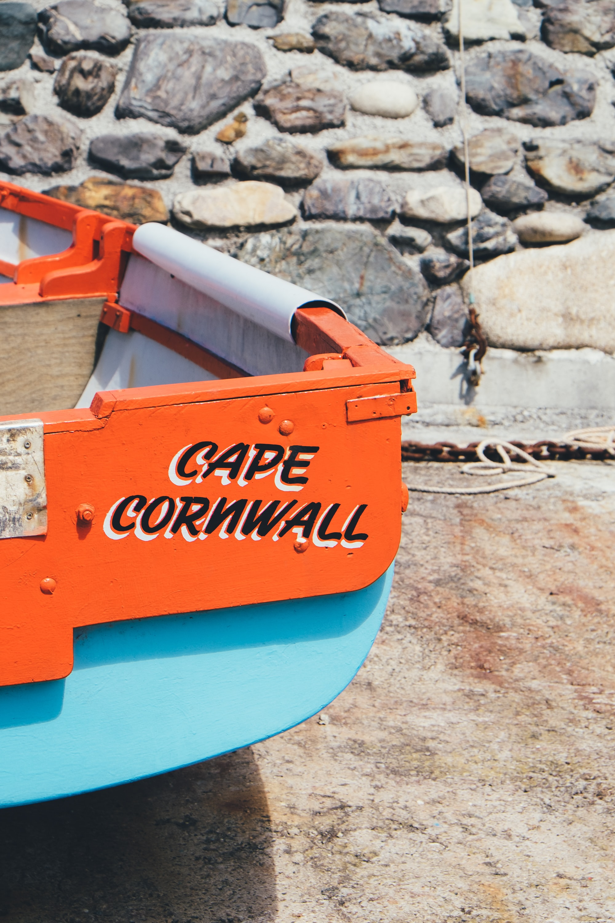 red and teal Cape Cornwall rack near stone wall