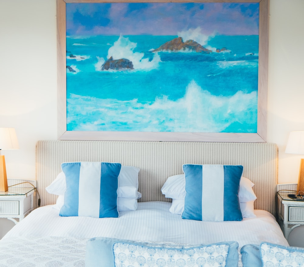 ocean with rocks painting on wall near bed