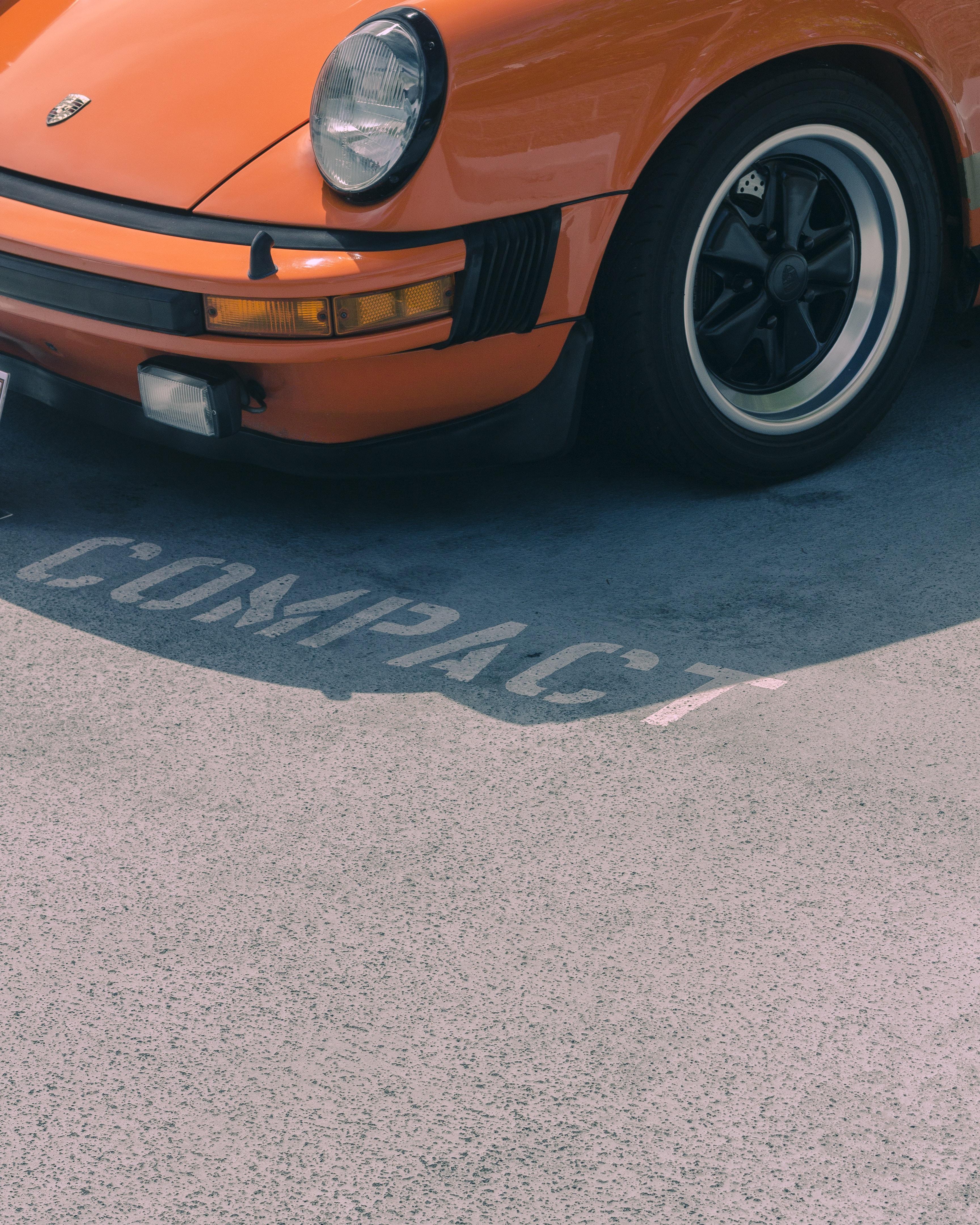 orange Porsche vehicle on Compact parking lot