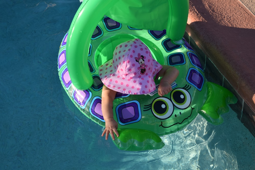 toddler riding on blue floating buoy during daytime