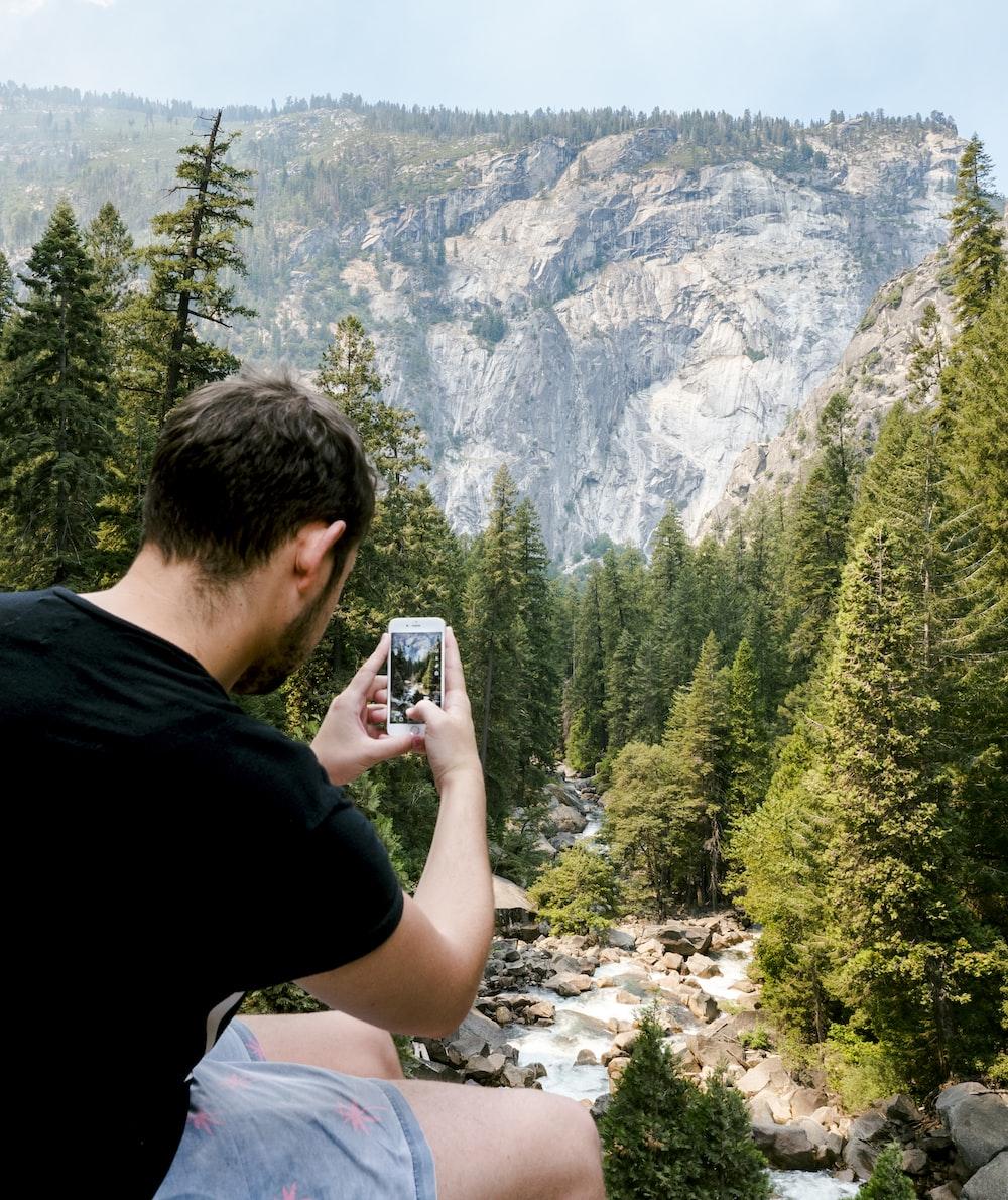 man holding white smartphone capturing tree