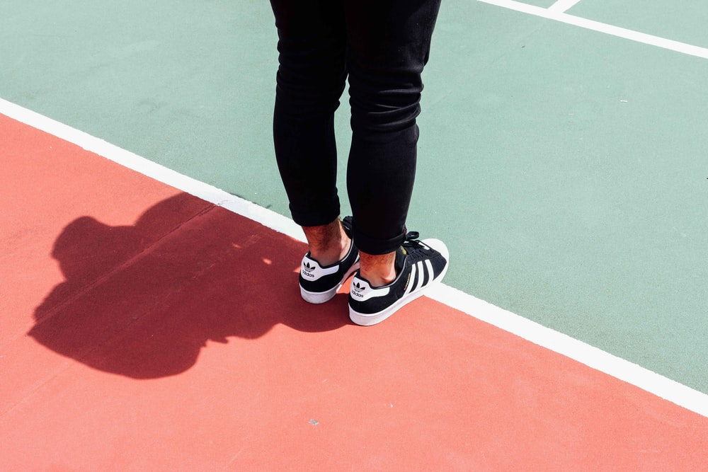 person wearing black adidas sneakers