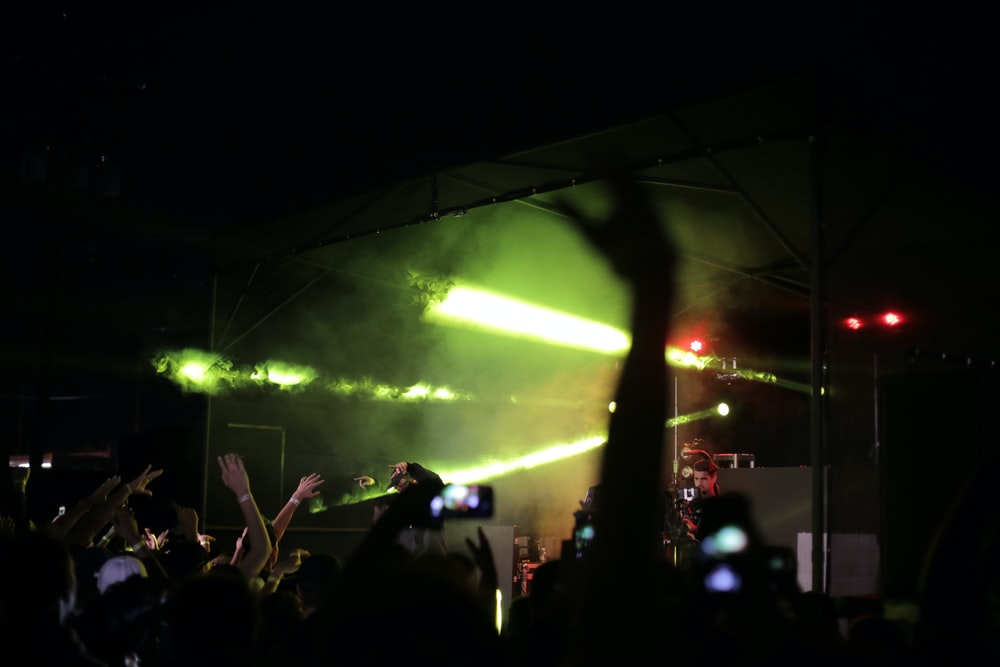 silhouette of crowd raising hands fronting concert stage