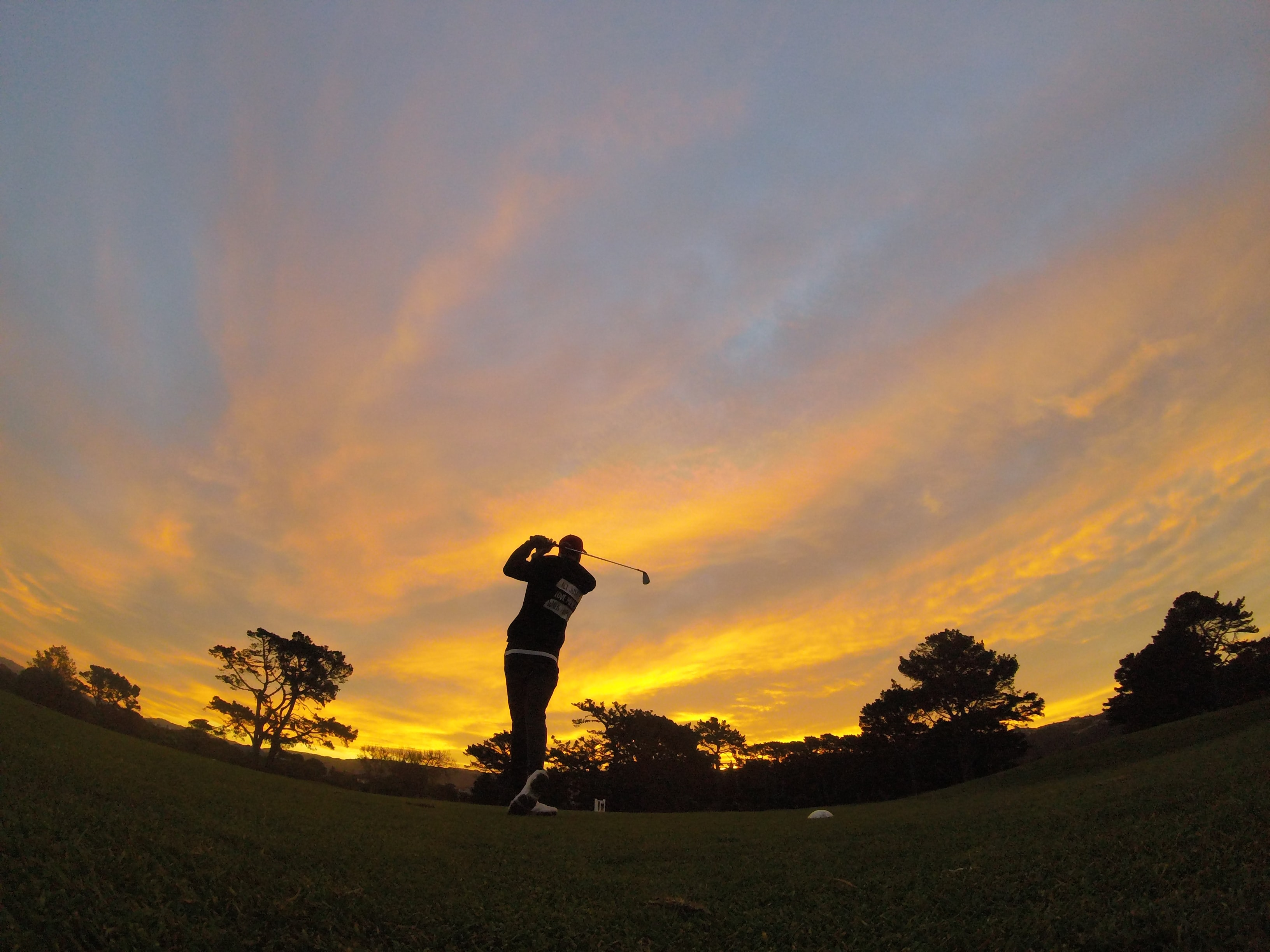 silhouette of man holding golf club
