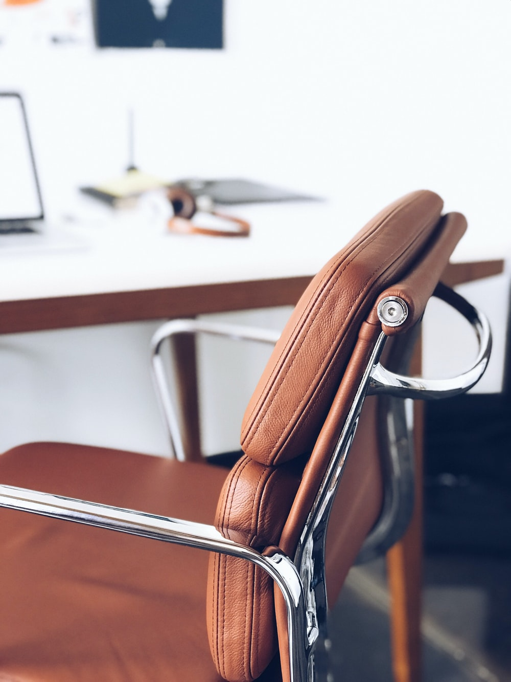 closeup photography of brown leather chair near white table