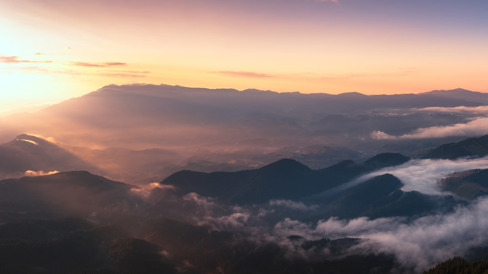 silhouette of mountain with fog at golden hour