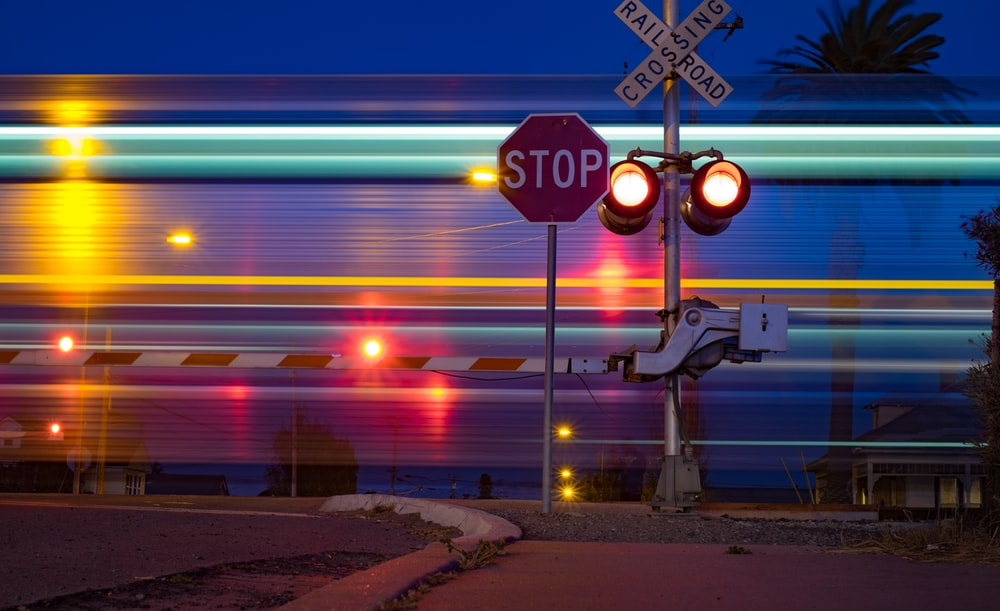 stop signage beside crossing railroad road sign at nighttime