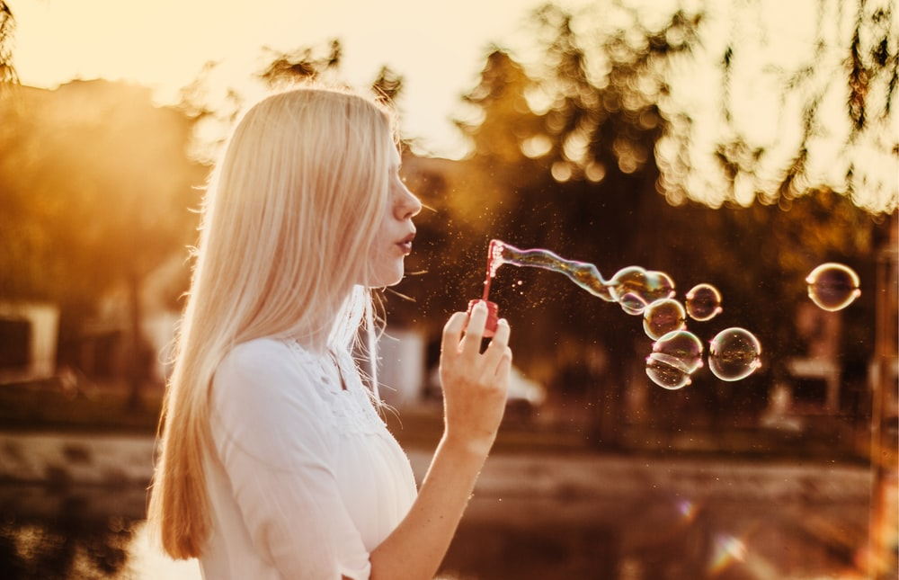 woman blowing bubbles during sunset