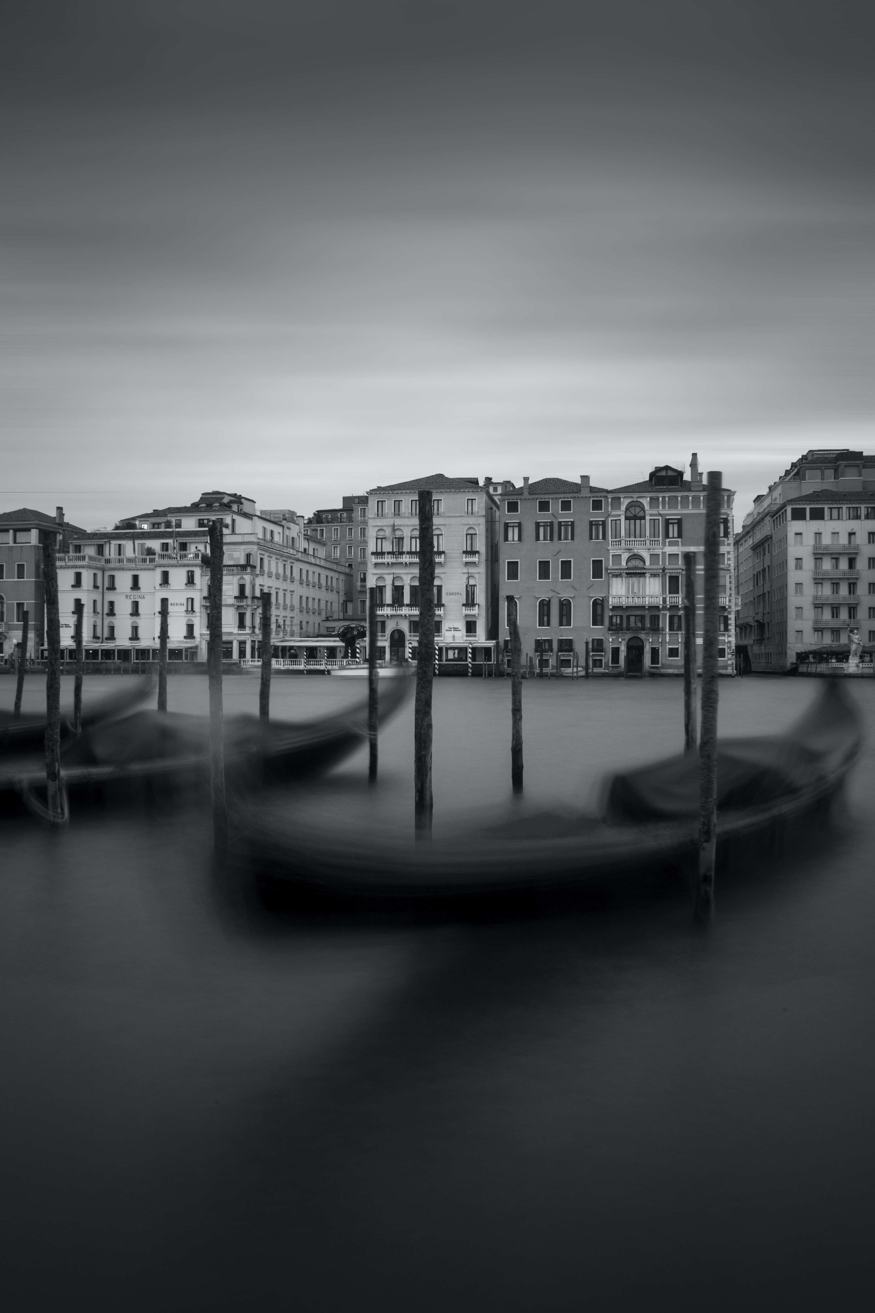 grayscale photography of two canoe in front of city buildings