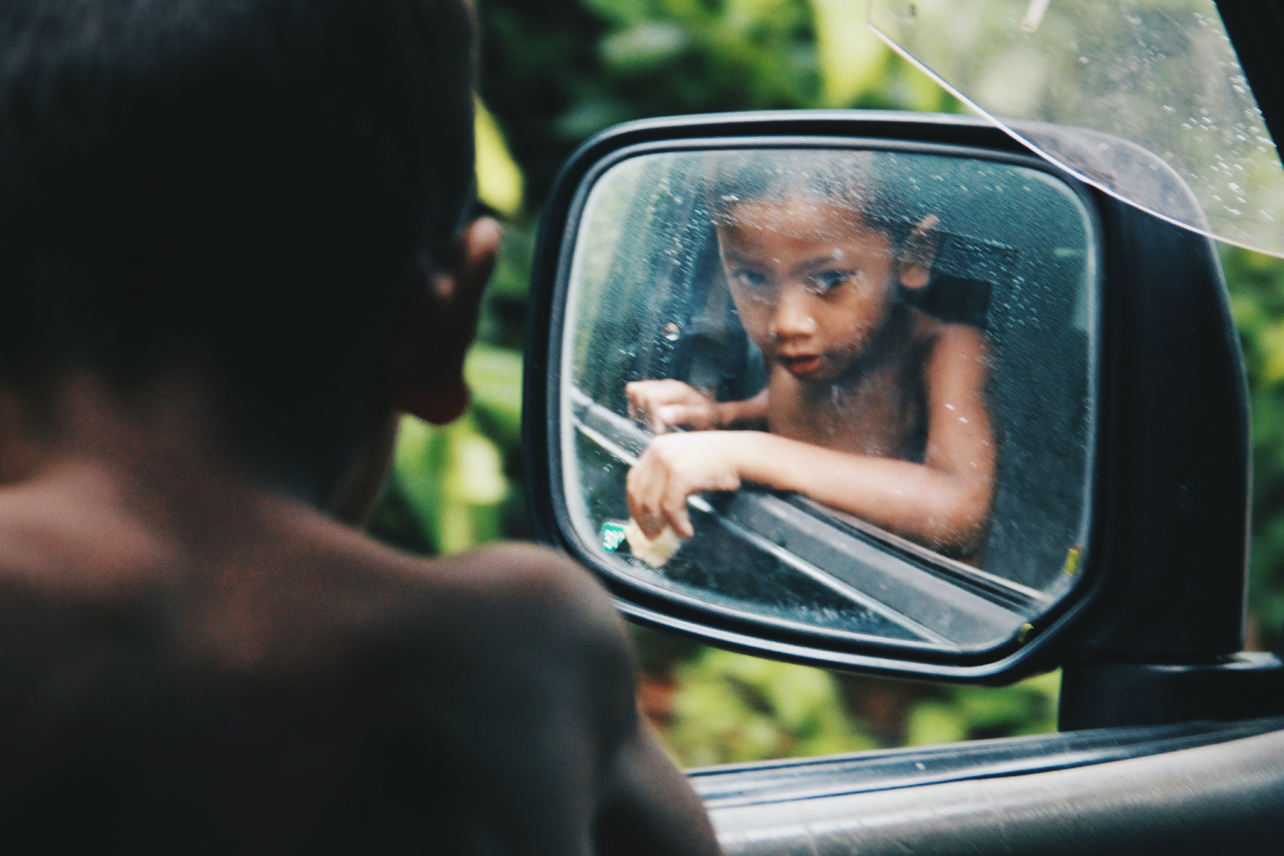 toddler looking at his reflection on wing mirror during daytime