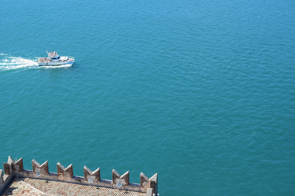 white motor boat sailing on ocean during daytime