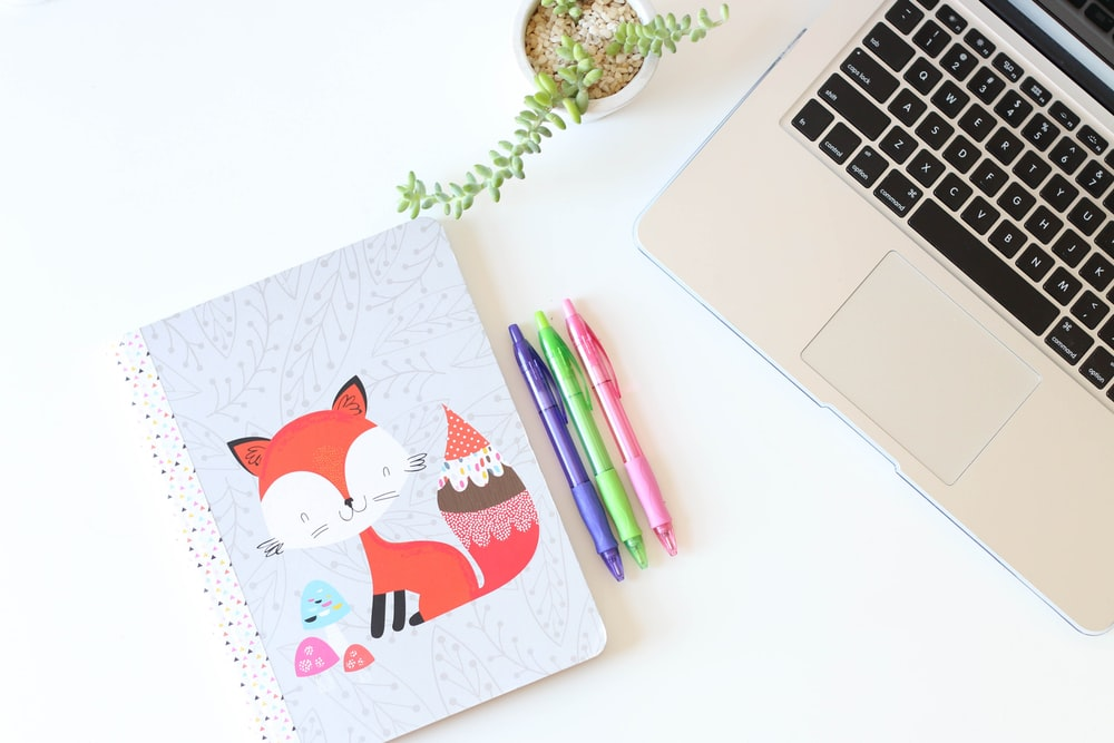 three assorted-color click pens between notebook and MacBook