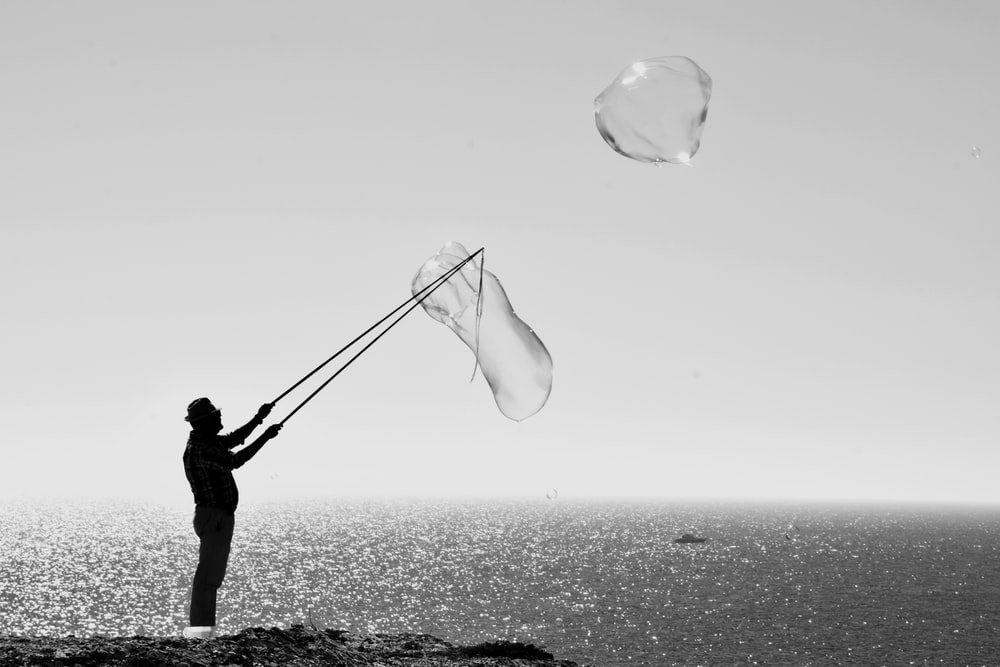 man holding stick making bubbles beside body of water