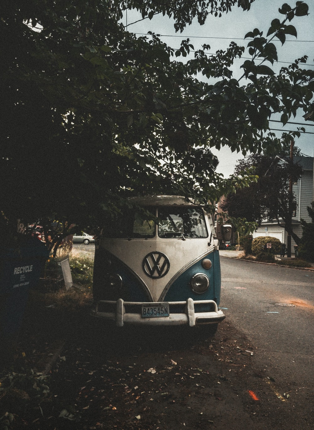 white and blue Volkswagen van park beside road