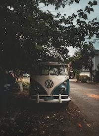 white and blue Volkswagen van park beside road