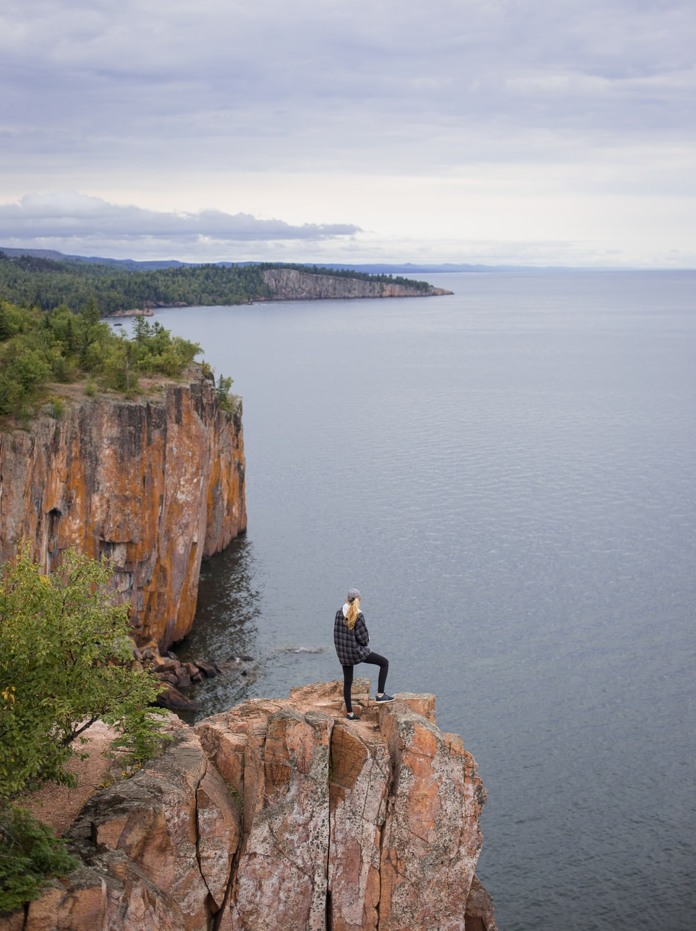 woman standing on cliff near body of water during daytime