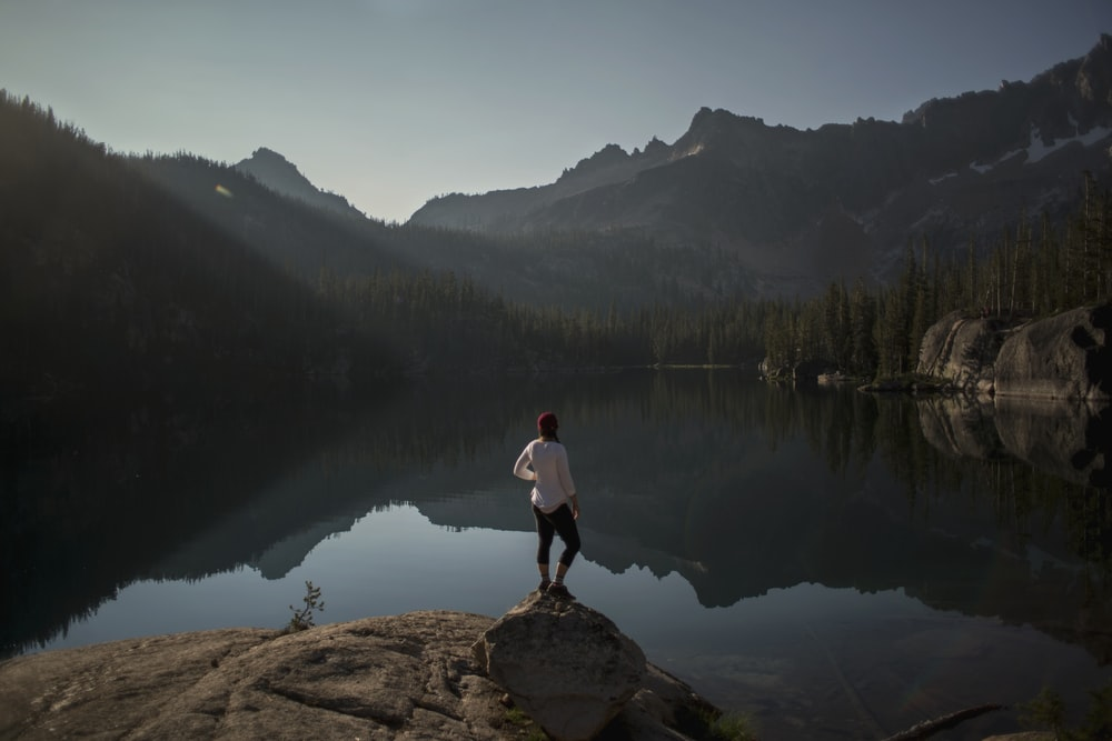 person standing on cliff near lake