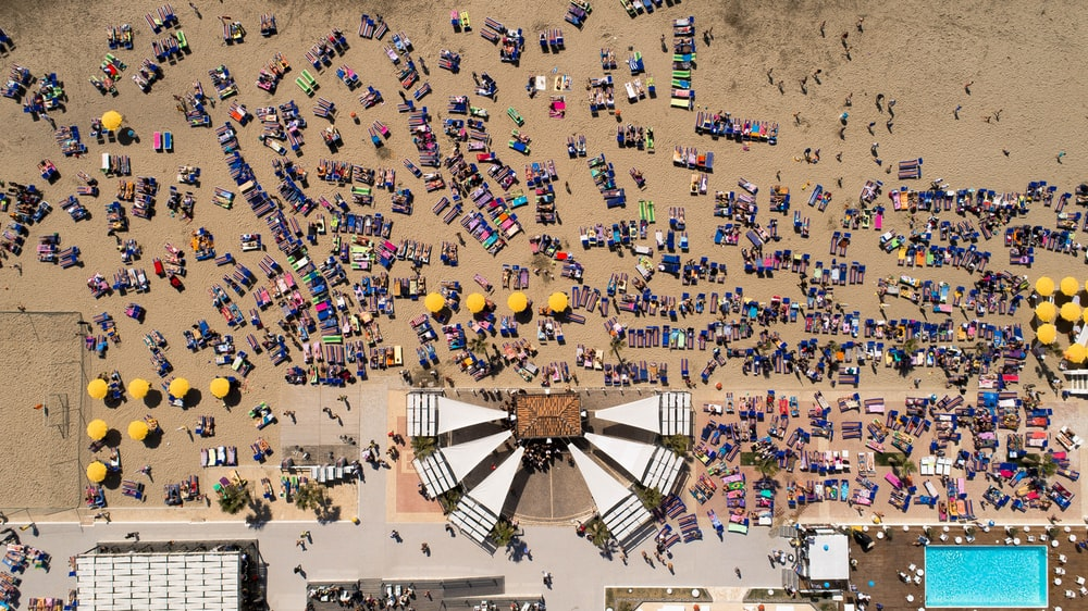 bird's eye view photography of beach umbrella filled with people