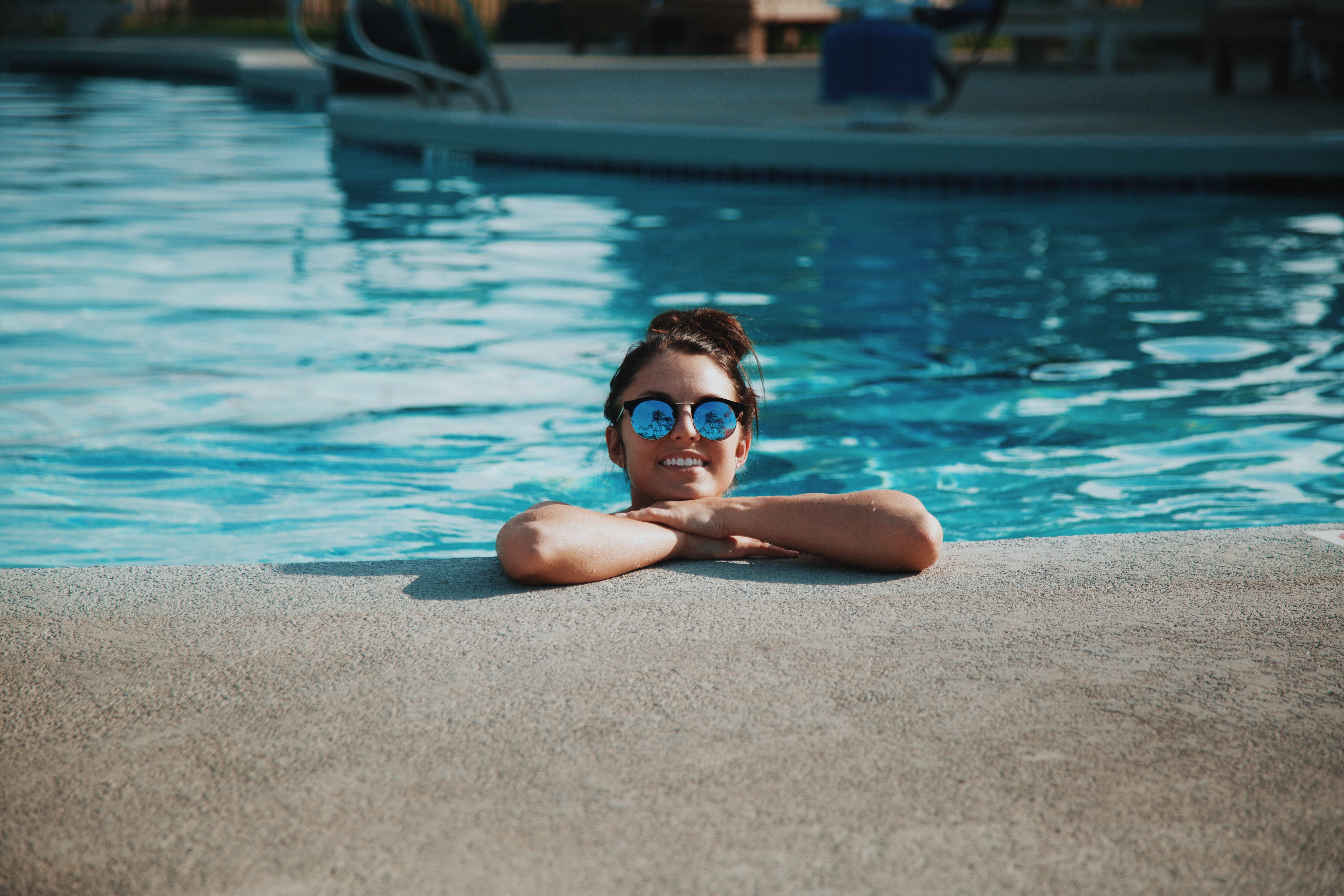 woman wearing sunglasses on swimming pool during daytime