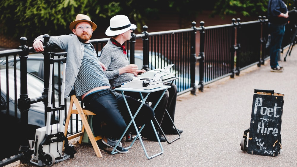 two men sitting on bench while leaning on metal rail near poet hire signboard during daytime