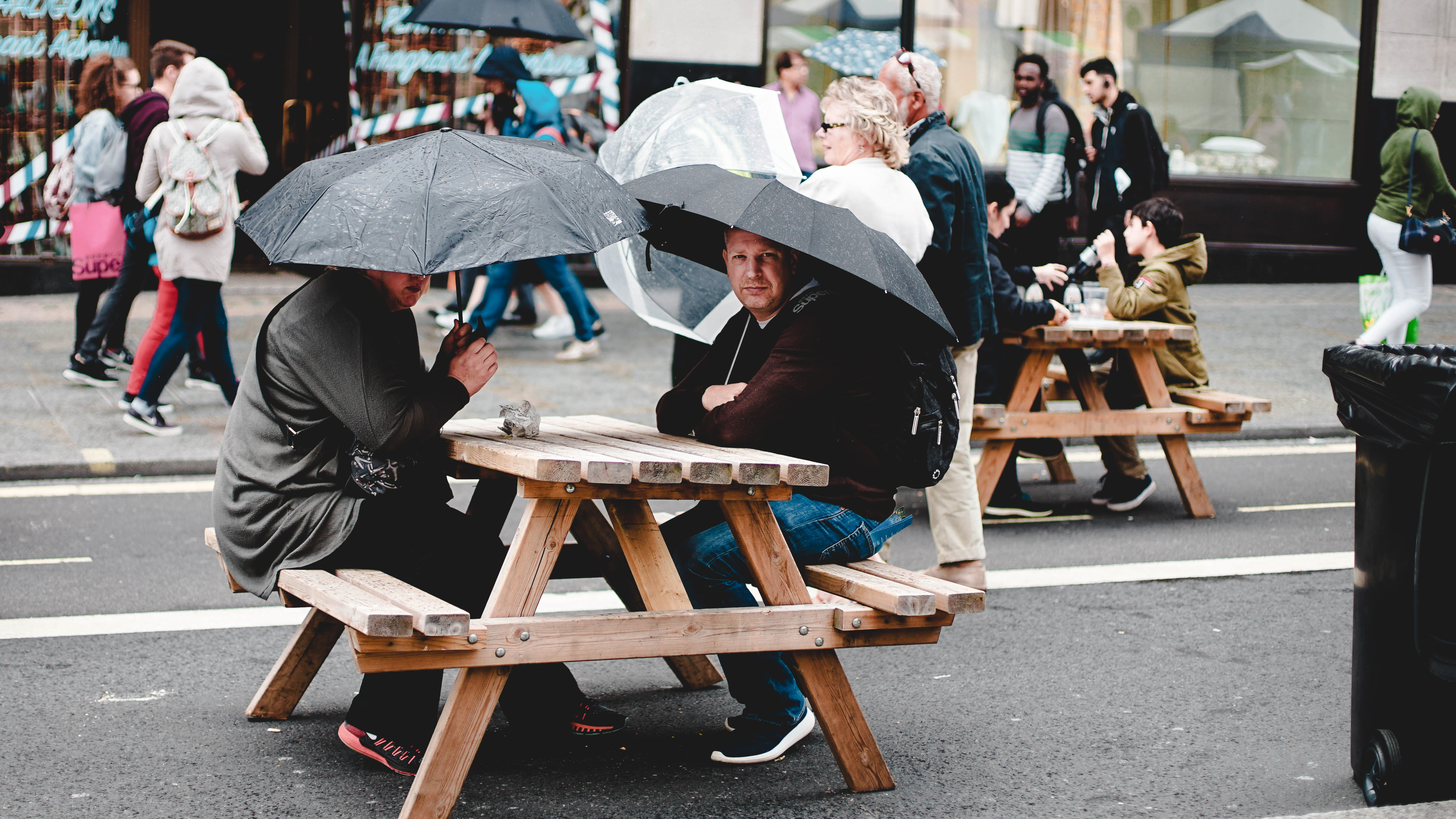 two man seating on brown picnic table under black umbrella