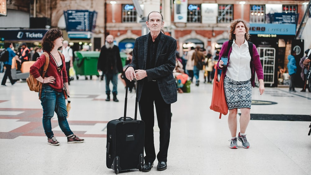standing man holding it's luggage bag